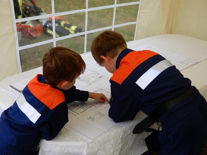 Mitglieder der Jugendfeuerwehr schauen sich die Pläne für das neue Gerätehaus ganz genau an